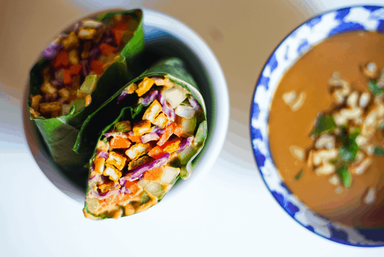Colorful vegetarian rainbow wraps made from collard green leaves next to a bowl of peanut sauce garnished with cilantro and chopped peanuts.