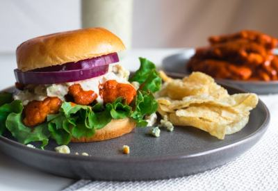 Buffalo chicken sandwich with green leaf lettuce, red onions and smoky blue cheese dressing with a side of chips.