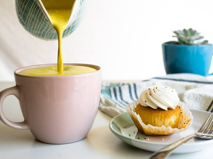A frothy bulletproof golden milk latte being poured into a mug next to a cupcake.