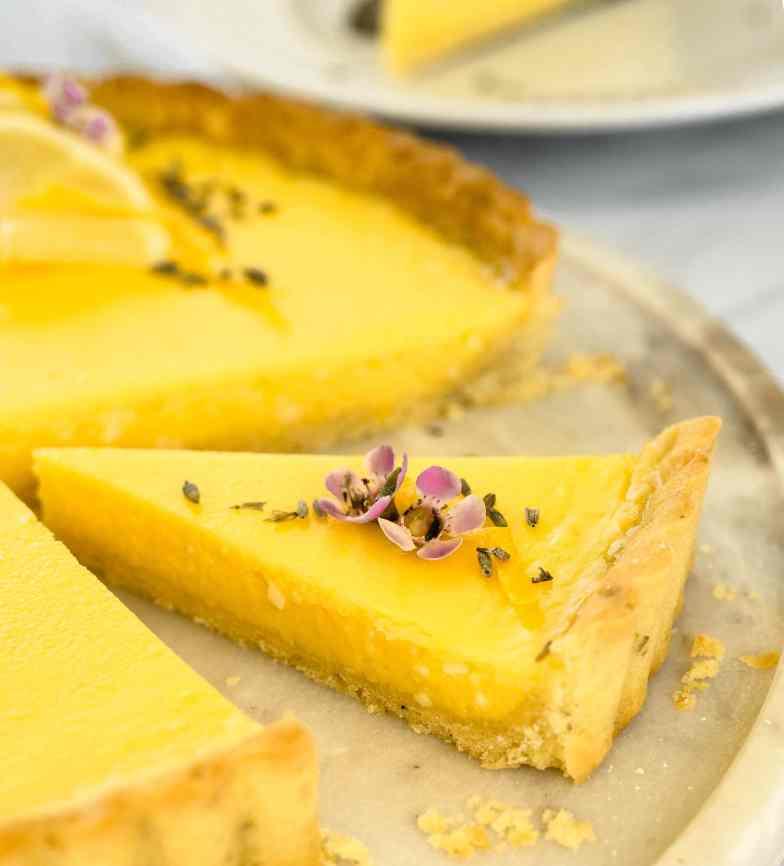 Close up of a slice of lavender lemon tart on a marble platter cut from center of tart.