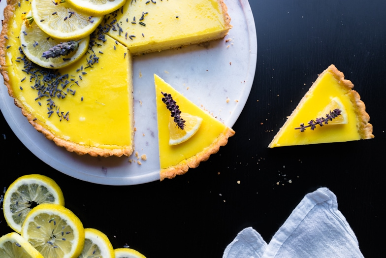 Lavender lemon tart with two slices cut out with a lemon wedge and flower garnish on top.