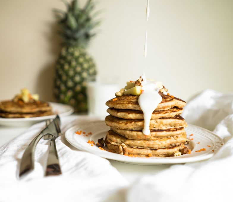 Stack of carrot cake pancakes with pineapple cream cheese drizzle being poured over the top.