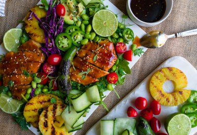 Colorful teriyaki chicken salad with grilled pineapple and fresh lime.