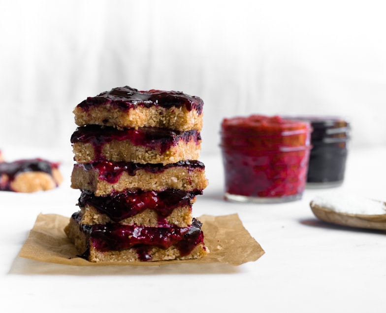Stack of healthy coconut lemon bliss bars with strawberry and blueberry compote.