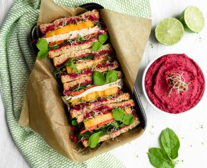 Rainbow veggie and turkey sandwich next to bowl of vibrant roasted beet hummus.