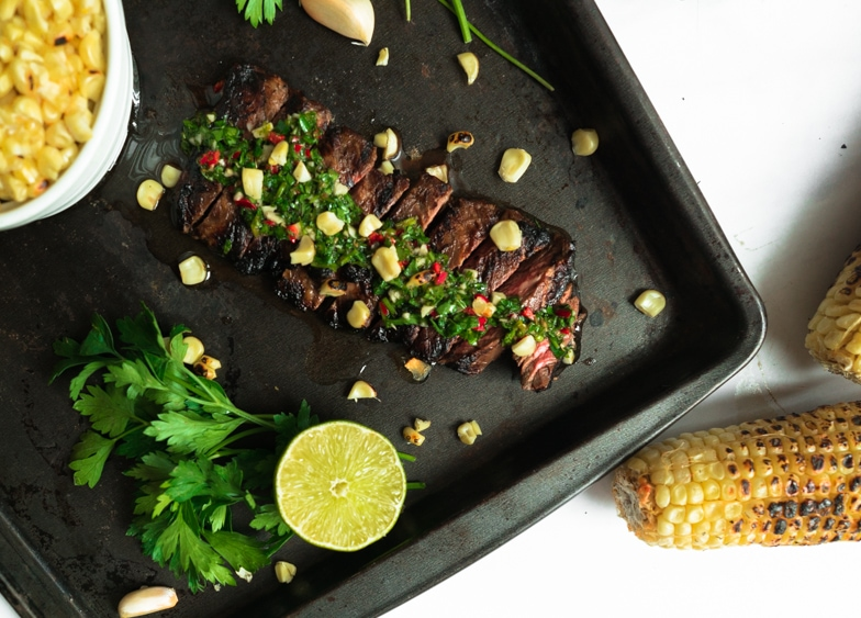 Sliced skirt steak with chimichurri served with charred corn on the cob.