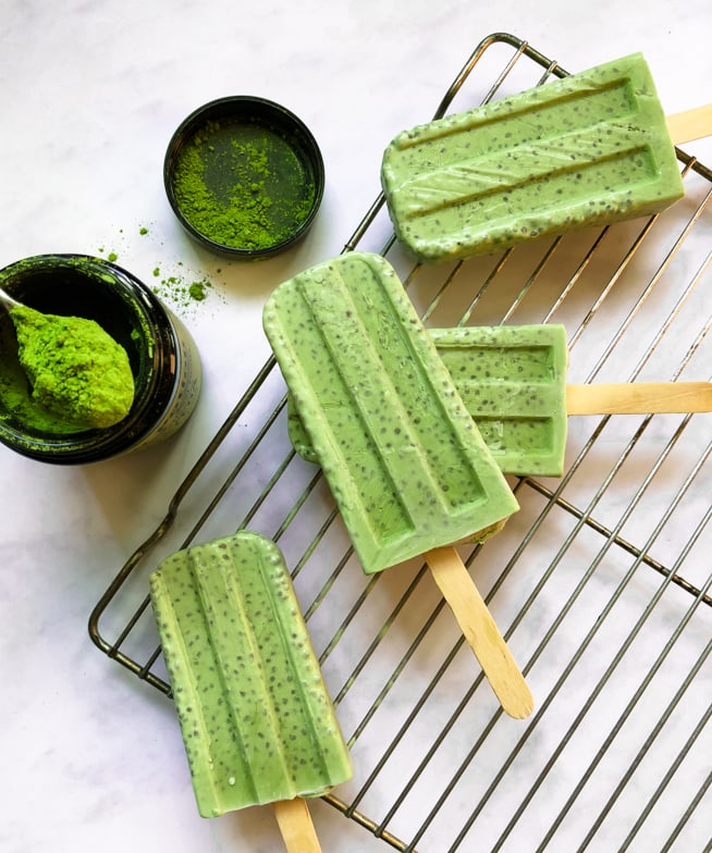 Matcha chia pudding popsicles next to a jar of vibrant green ceremonial grade matcha.