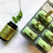 Matcha chia pudding popsicles next to a jar of vibrant green Sun Potion matcha.