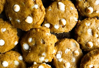 Tray of freshly baked gluten-free pumpkin cookies with white chocolate chips and macadamia nuts.