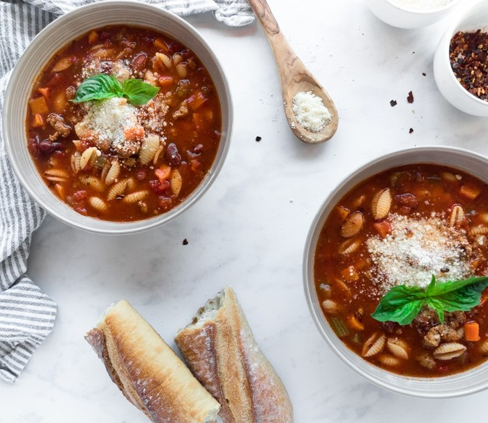 Two bowls of spicy pasta e fagioli with parmesan cheese, basil, and rustic bread.