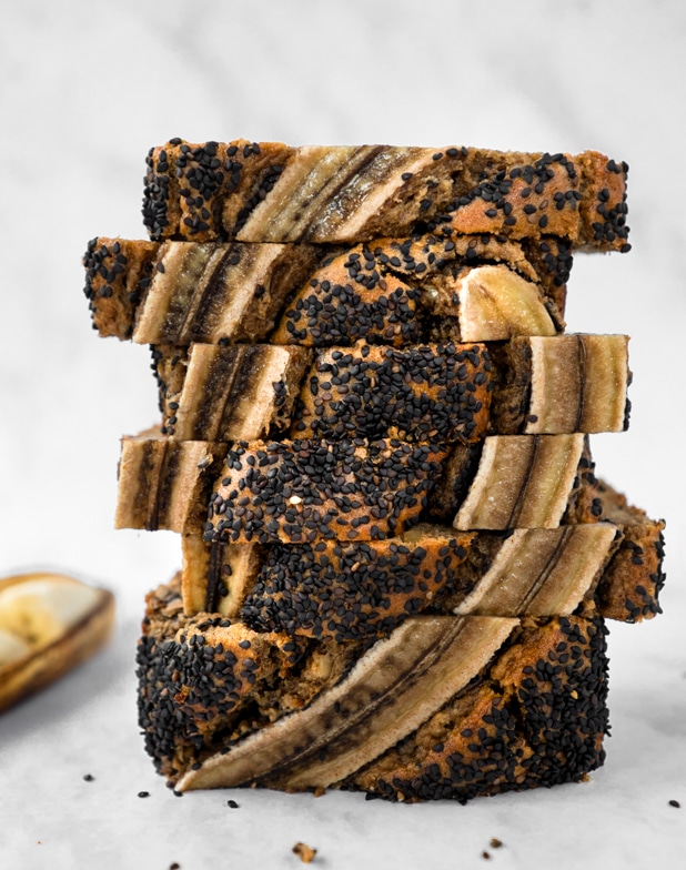 Loaf of chai tahini banana bread cut into thick slices and stacked vertically in a zigzag pattern.