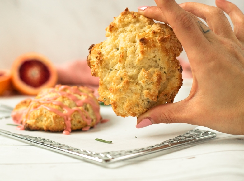 Hand grabbing a rosemary Irish soda scone off the table.