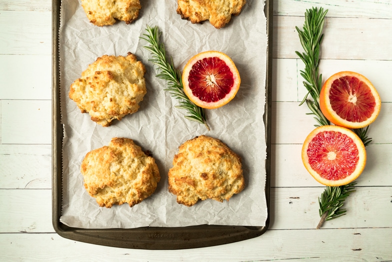Sheet pan with freshly baked Irish soda scones next to sprigs of rosemary and fresh blood oranges.