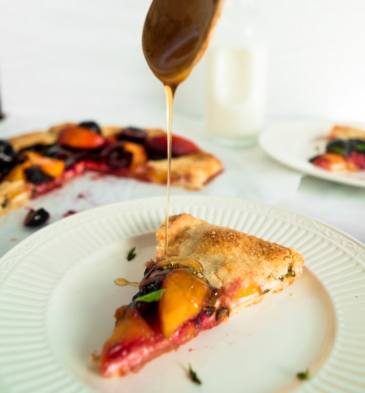 Slice of cherry peach goat cheese galette with spicy pepper jelly being drizzled with honey.