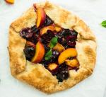 Cherry peach goat cheese galette with spicy pepper jelly, garnished with fresh basil.
