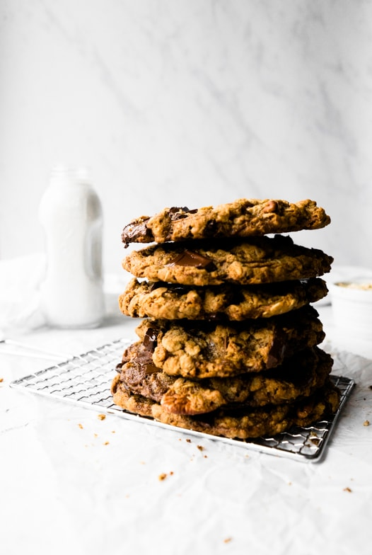 Tall stack of bakery-style pumpkin spice oatmeal cookies with melty chocolate chunks and pecans, and a large glass of milk in the background.