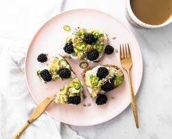 Slices of avocado toast with blackberries, serrano peppers, and honey black pepper whipped ricotta, on a plate near a cup of coffee.