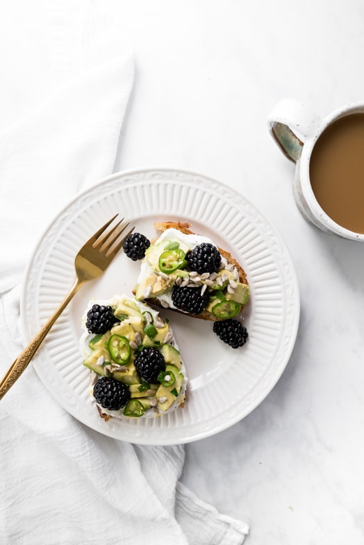 Two slices of avocado toast with blackberries, serrano peppers, and honey black pepper whipped ricotta, on a small plate near a cup of coffee.