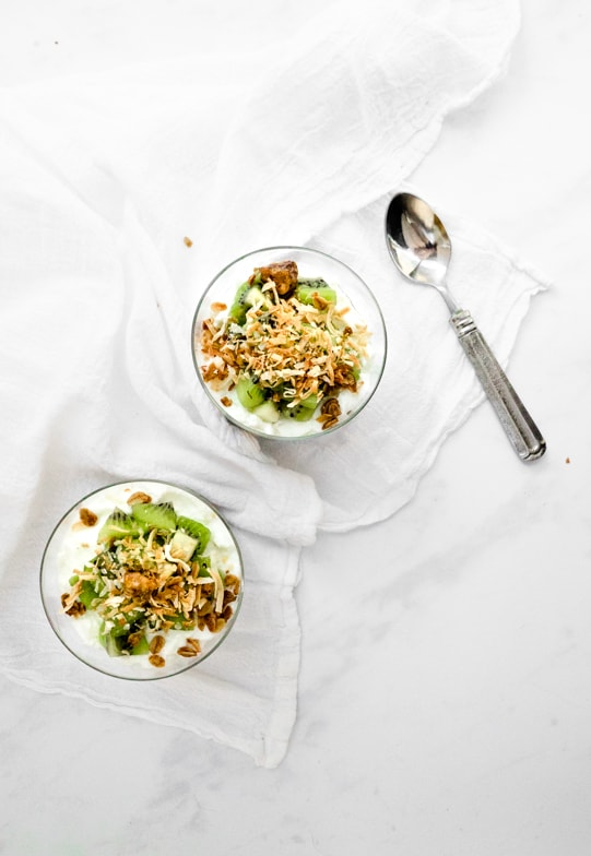 Two tropical fruit parfaits topped with kiwi, toasted coconut, and crunchy honey ginger granola.