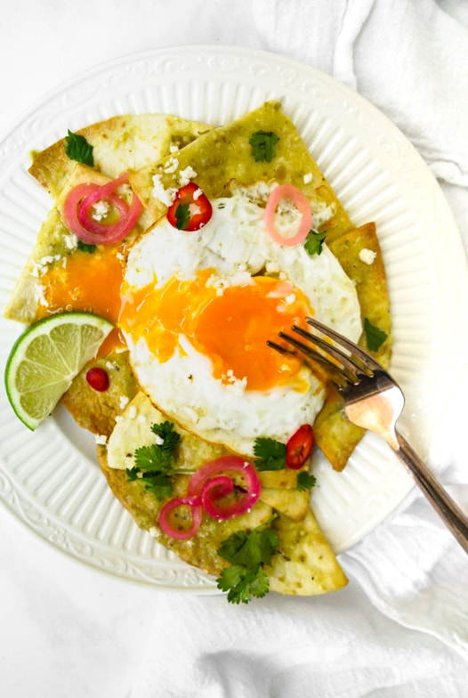 Plate of air fryer chilaquiles verdes with pickled red onions topped with a yolky sunny side up egg that's broken into with a fork.