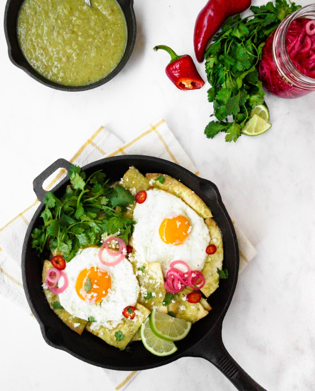 Skillet of air fryer chilaquiles verdes with sunny side up eggs and pickled red onions, topped with cilantro and lime wedges.