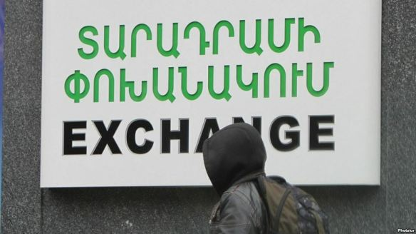 Armenia - A schoolboy walks past a currency exchange sign in Yerevan, 17Dec2014.