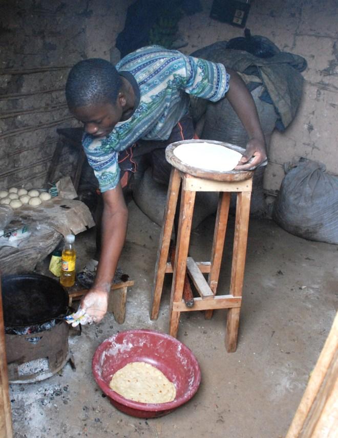 En lokal mann lager chapatti i Uganda