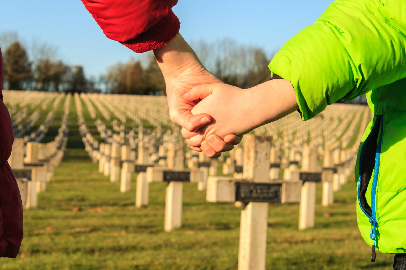 family holding hands at veterans grave