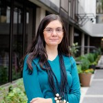 Native American woman with brown hair and glasses in a teal shirt and black necklace standing in front of a building and potted plants.
