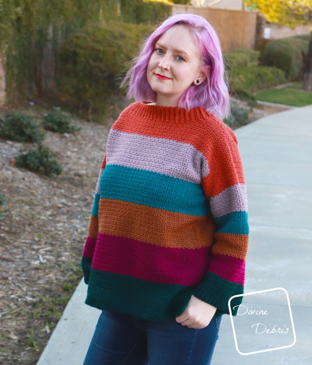 [image description] White woman with pink hair stands facing the camera in striped crochet Amelia Pullover crochet pattern  in front of a wall of ivy