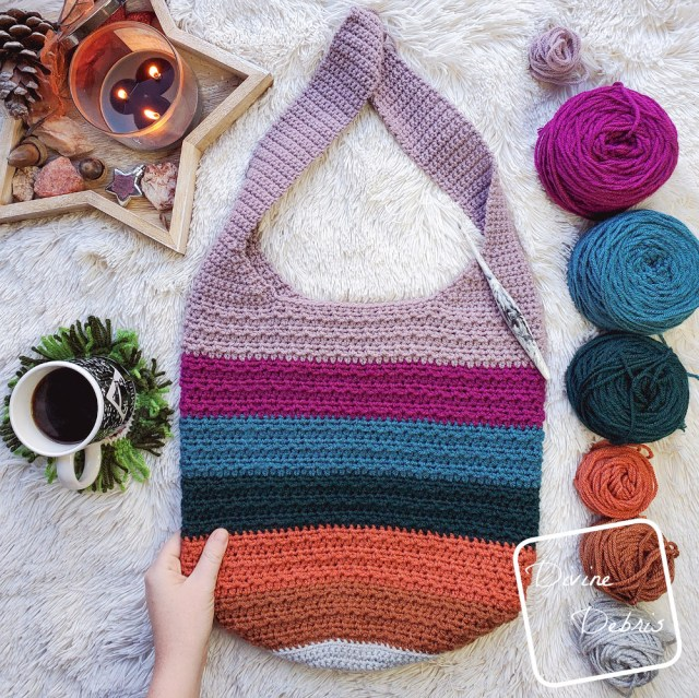 [Image description] Striped Alix Bag lays in the center on a white fur blanket, one hand holding it on the left bottom side. Yarn cakes are in line on the right side, a cup of coffee and a star platter with a candle on it lay on the left.