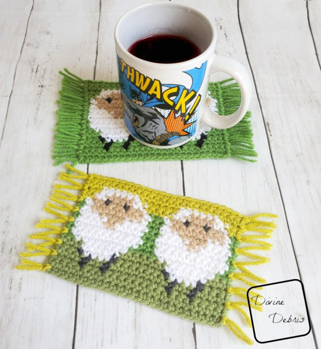 [image description] One sheep mug rug is in the foreground, green background of white sheep, with one in the background and a Batman coffee cup on it, mug rug is a white sheep on a green background, with fringe on the side. The Dancing Sheep Mug Rug
