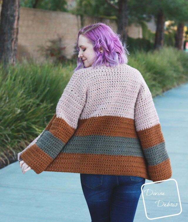 [image description] white woman with purple hair facing away looks down and over her shoulder  while wearing the striped Mia Cardigan crochet pattern while standing in front of a row of bushes.