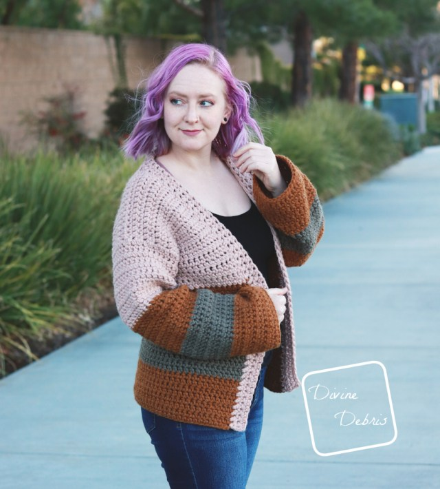 [image description] white woman with purple hair looks off to the left while wearing the striped Mia Cardigan crochet pattern while standing in front of a row of bushes.