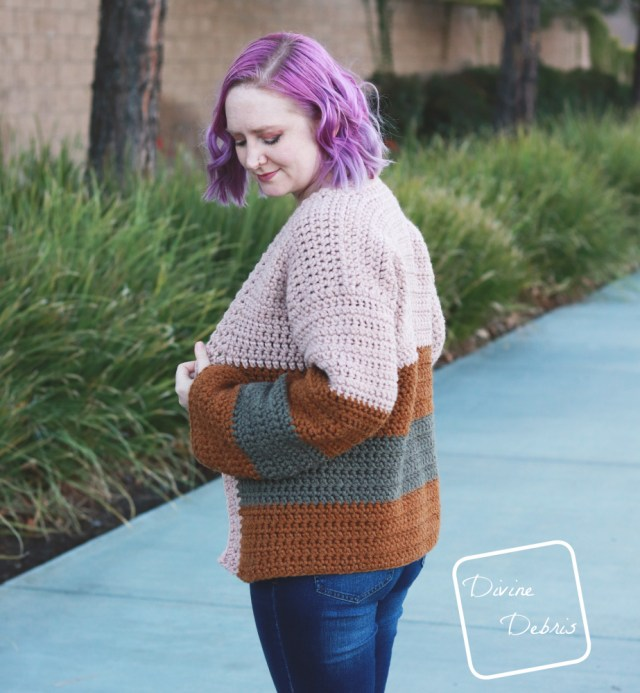 [image description] white woman with purple hair looks down while wearing the striped Mia Cardigan crochet pattern while standing in front of a row of bushes.