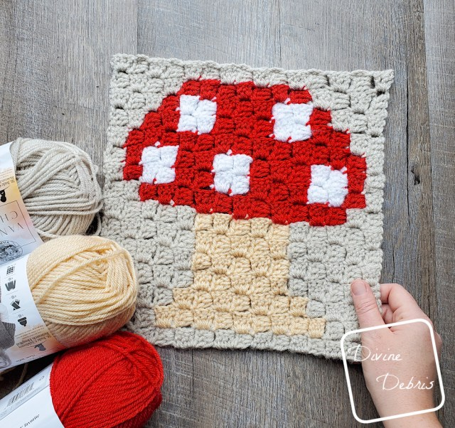 [Image description] C2C Mushroom Afghan Square laying in the center of the frame on a wood-grain background. One hand holding the bottom right corner and 3 skeins of yarn(red, tan, and beige) on the bottom left corner.