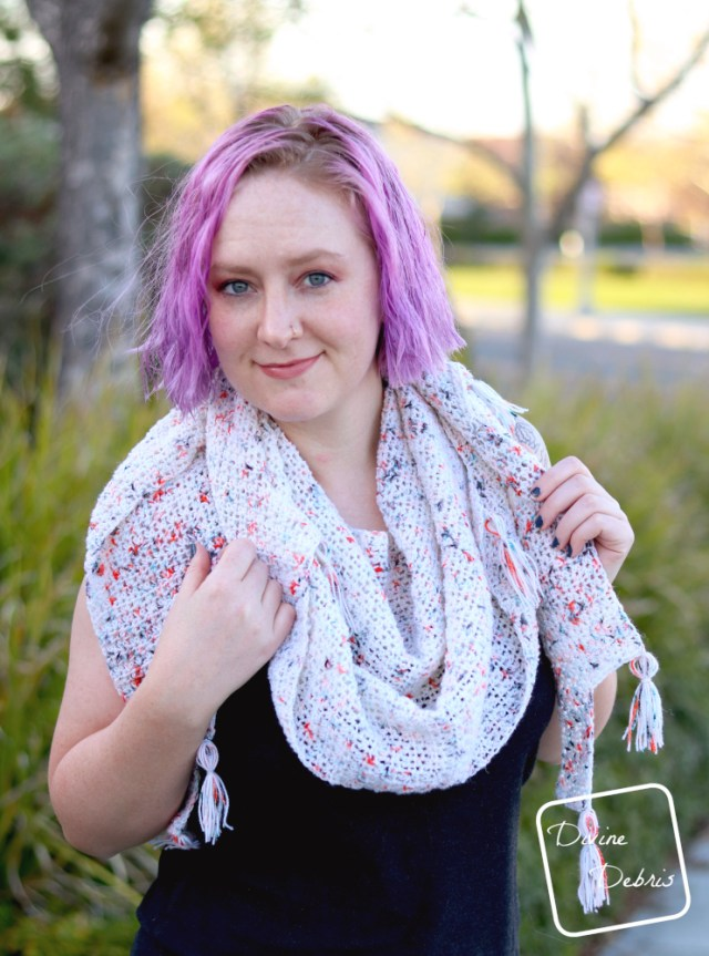 [image description]White woman with purple hair smiles at the camera while wearing Lois Shawl wrapped around her neck, holding onto it with both hands
