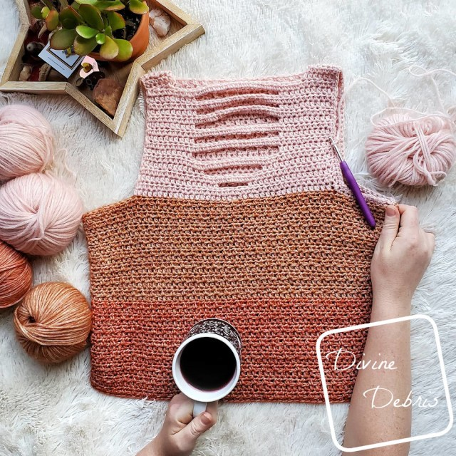 {image description] the Alix Tank top lays in the center of the frame, a white woman's hand crasps the right side and holds a cup of coffee over the bottom of the top.