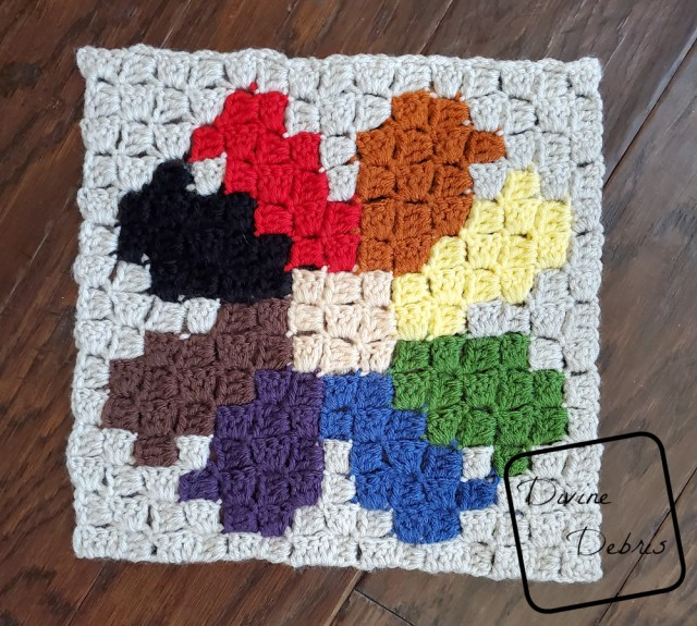 [Image description] the C2C Daisy Afghan Square lays on a wood background .