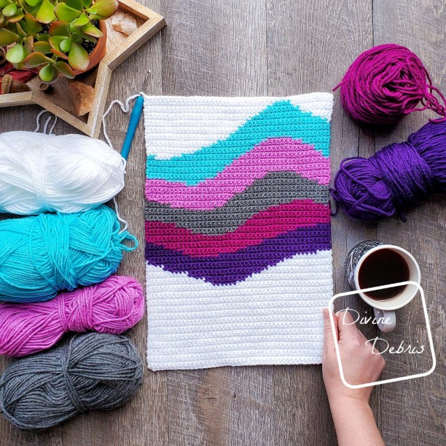 [Image description] the 6 color Cool Waves Wall-Hanging lays in the middle of the frame, 4 skeins of yarn on the left and 1 cake and a skein on right next to a cup of coffee. A white woman's hand is holding onto the lower right-hand side.
