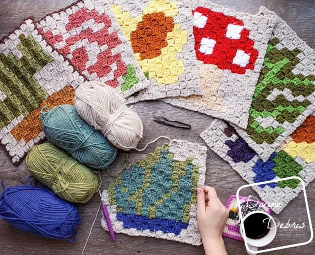 [Image description] the C2C Agave Square lays half-finished flat on a wood grain background, a white woman's hand holds the bottom right corner, 4 skeins of yarn sit on the left and a fan of the previous c2c squares around the top of the photo