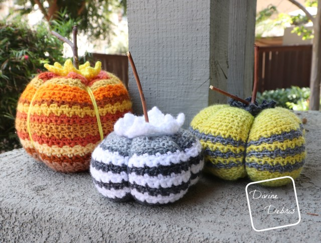 [Image description] 3 different Amelia Pumpkins (black and white in the center, green and grey on the right, and many oranges on the left) sitting in front of a grey wood pillar and trees.