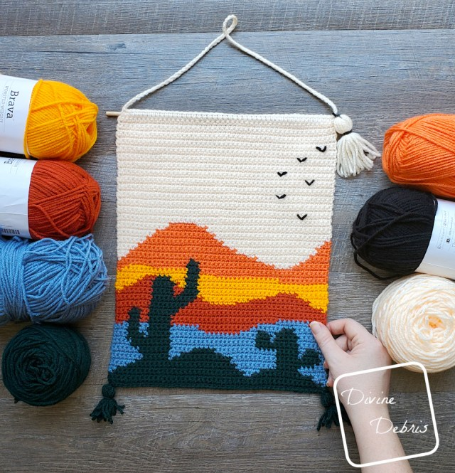 [Image description] the Cool Cactus Wall-Hanging lays in the center of the photo on a wood grain background, with 4 skeins of yarn on the left and 3 skeins on the right and a white woman's hand holding the bottom right corner.