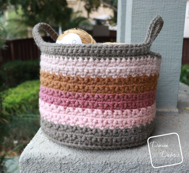 [image description] Amelia Basket crochet pattern with a couple skeins of yarn in side, sitting on a grey platform and bushes on the left side of the photo