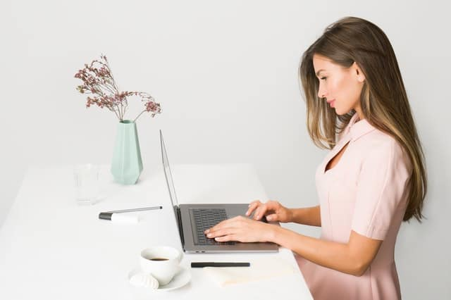 woman in pink dress using laptop computer 1586973