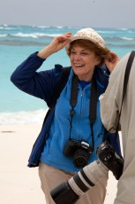 Dr. Sylvia Earle tries on a construction helmet found in plastic debris on Midway Atoll National Wildlife Refuge. Photo by Bonnie L. Campbell/USFWS