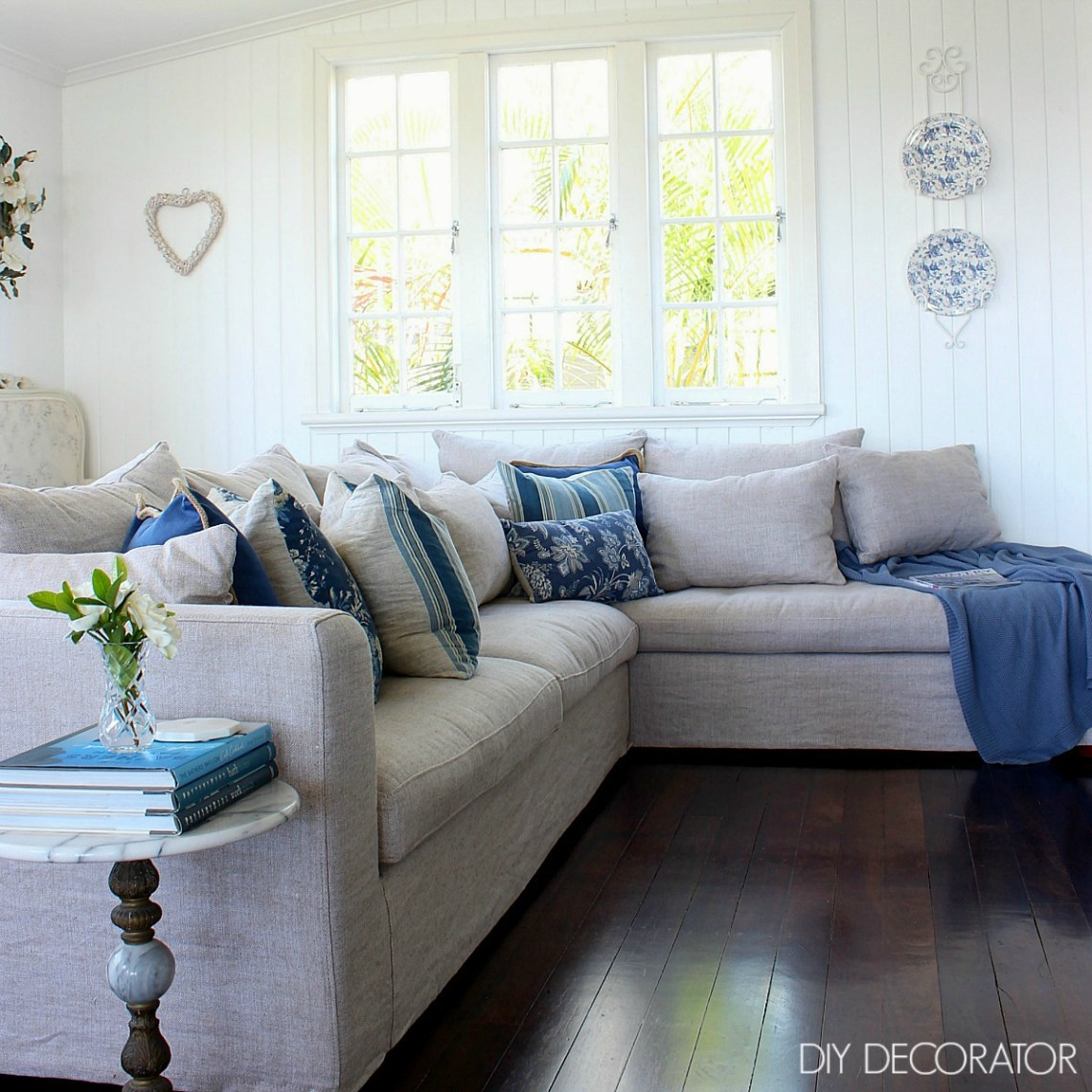Blue decorative cushions on a linen slipcover modular sofa. A love hate relationship with cushions