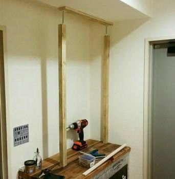 天井にクッションをあてて棒を突っ張る