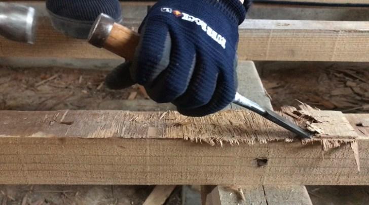 根太にボンドで引っ付いている木材をノミで引き剥がす