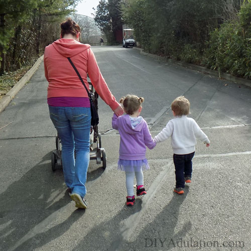 Mom and kids holding hands and walking